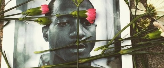 CREDIT: CHRISTOPHER MATHIAS/THE HUFFINGTON POST Flowers are scattered across a photo of Kalief Browder, who took his own life in June at the age of 22.