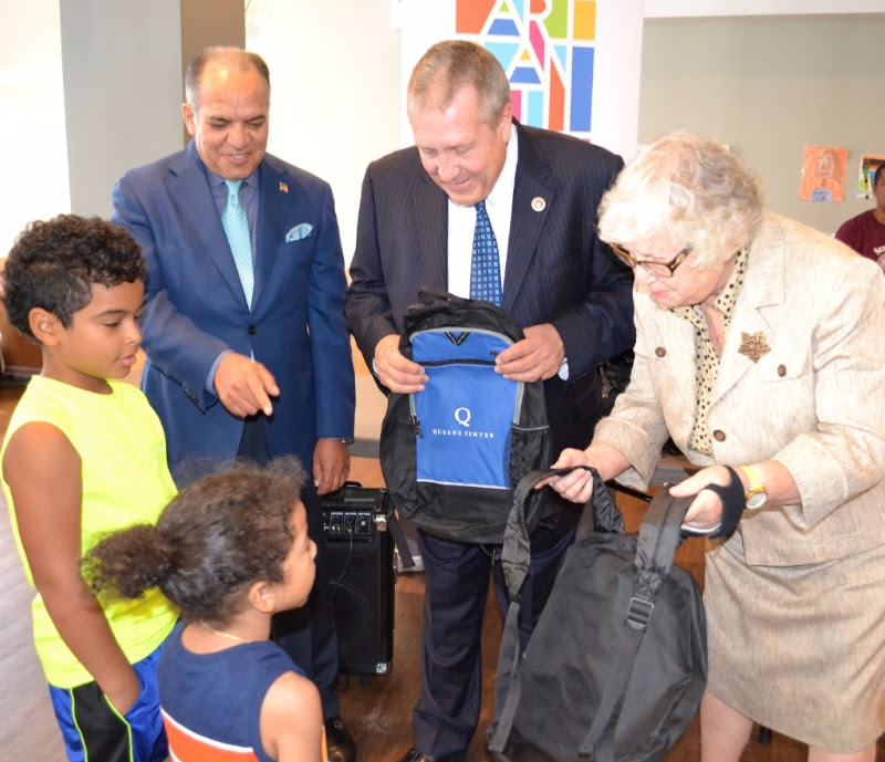 (L. to r.); Samaritan Village President and CEO Tino Hernandez, NYC Council Education Committee Chairperson Daniel Dromm and state Senator Toby Ann Stavisky deliver free backpacks and other school supplies donated by Queens Center Mall to students at the Pan Am Boulevard Family Transitional Residence.